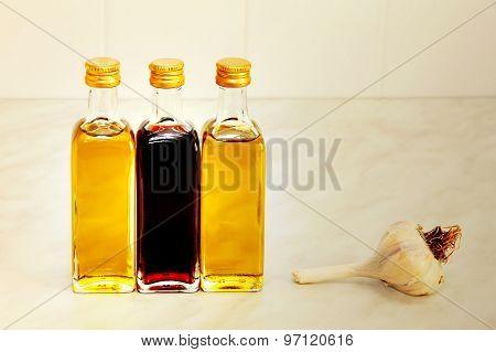 Three Olive Oil Bottles And Garlic On Kitchen Table Taken Closeu