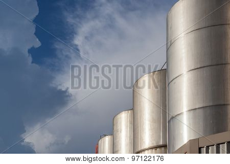 Row Of Huge Petrol Oil Tanks In Refinery Industry With Beautiful Blue Sky.