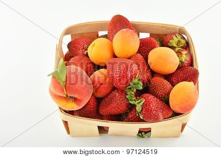 Strawberries, Apricots And Peach In Wooden Basket Isolated On White