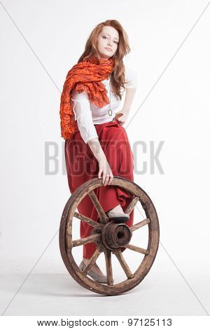 Young woman in long red skirt standing near the wheel of the cart