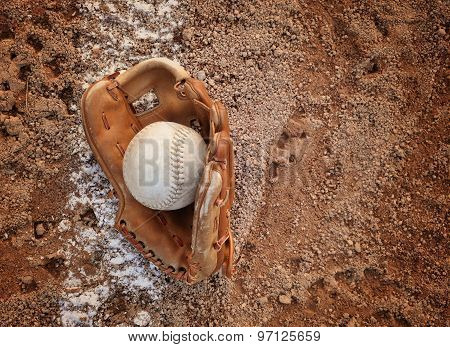 A closeup of an old baseball and glove on a dirt background with copyspace for a message for a sport or recreation concept.