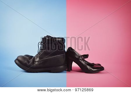 A man's boots and woman's high heels are fighting against a blue and pink isolated background for a struggle or gender power concept.