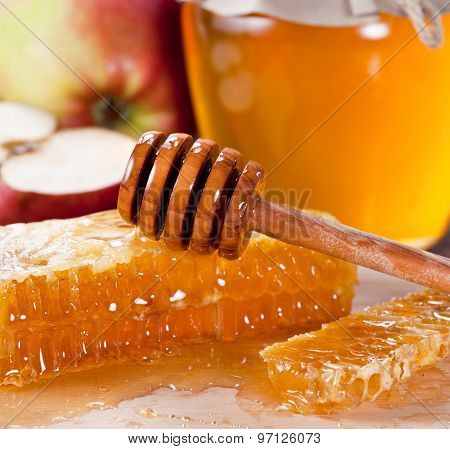 Honeycombs and wooden dripper. Honey can and apple on the background.