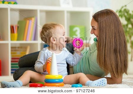 cute mother and baby boy play together indoor at home