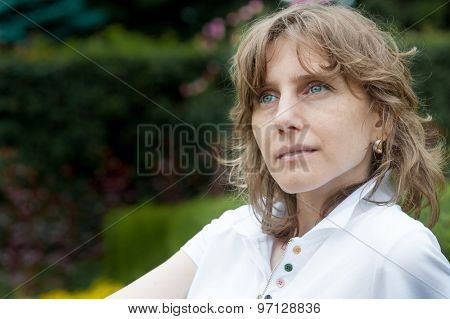 Sad middle age woman portrait in a park