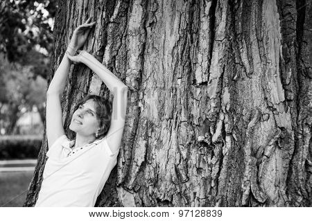 Middle age woman relaxes in a park. Black and white