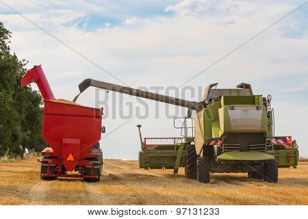 Combine Harvester And Tractor's Trailer Full Of Wheat Grains