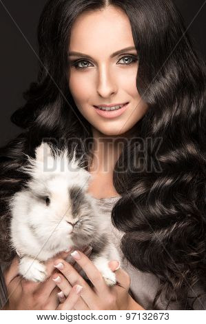 Beautiful girl brunette model, perfect curls and evening fashion make-up with a rabbit in her hands.