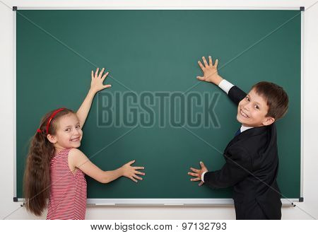 boy and girl write on school board