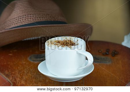 Cappuccino coffee cup, guitar and hat