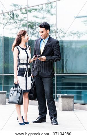 Asian business woman and man  with mobile phone in front of building