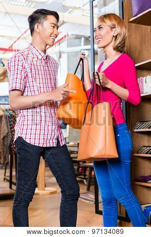 Asian couple shopping bags in store or shop