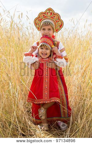 Two Girls In The Russian National Sundresses Play A Field Of Ripe Wheat