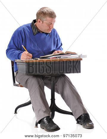 A mature student hard at work as he sits in a retro child's school desk,  On a white background.