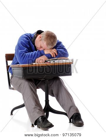 A mature man in an old school desk falling asleep on his pile of papers and books.  On a white background.