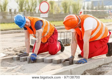 Construction Workers Putting Paving Stones