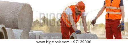 Construction Workers Rolling Concrete Circle