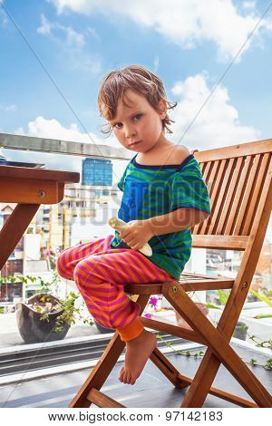 child eating a banana at balcony