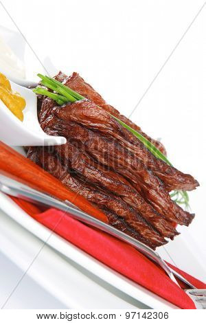 roast red beef meat fillet with red hot pepper with ketchup, mayonnaise, and mustard on plate isolated on white background
