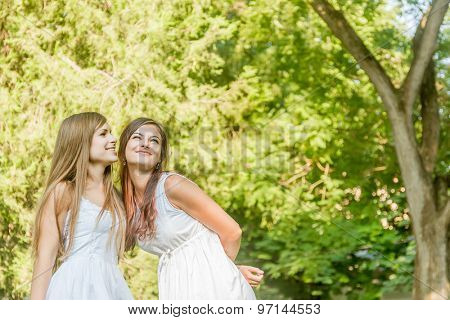 two young happy girls on natural green background, smiling happy girls outdoor portrait