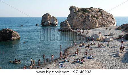 Tourists Swimming And Relaxing At Famous Rock Of Aphrodite Beach At Paphos Area In Cyprus