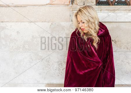 Woman in red cloak sitting on bench