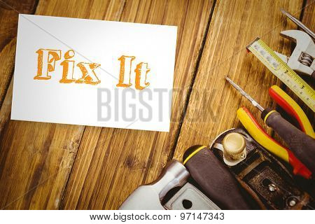 The word fix it and white card against desk with tools