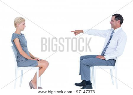 businessman pointing at businesswoman against a white wall