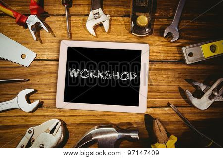 The word workshop and tablet pc against tools on desk