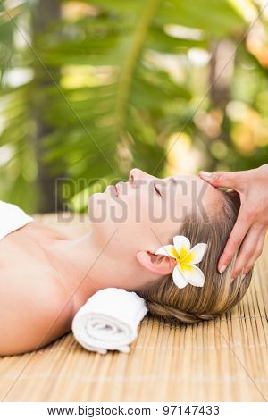 Close up of an attractive young woman receiving facial massage at spa center