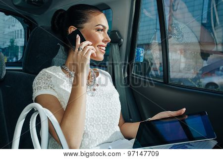 Young Businesswoman Talking On The Phone In The Back Seat Of The Car And Holding In Hand A Digital T