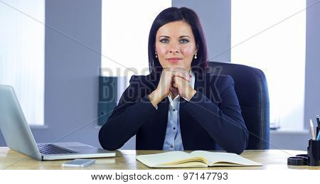 Confident businesswoman smiling at camera in her office