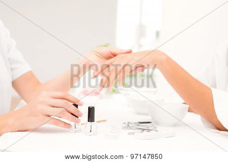 Close up of beautician filing female clients nails at spa beauty salon