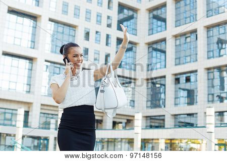 Young Business Woman Outside On The Phone And Shows  Hand Hello Sign