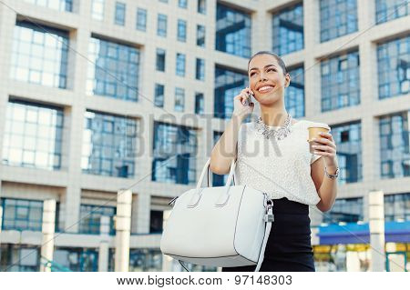 Young Businesswoman Holding Coffee To Go And Talking On The Phone