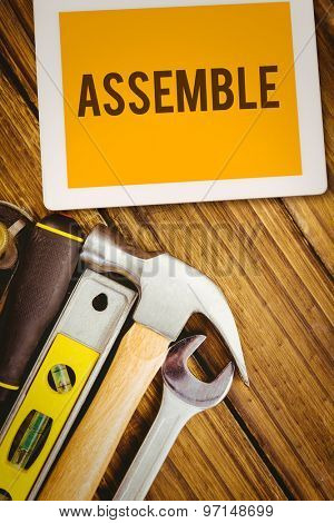 The word assemble and tablet pc against desk with tools