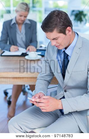 Businessman texting on his mobile phone in an office