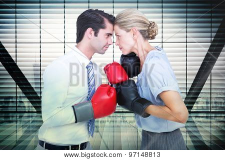 Business people wearing and boxing red gloves against window overlooking city