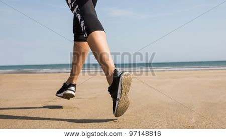 Fit woman jogging on the sand at the beach