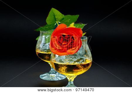 Two Glasses Of Cognac With Red Rose