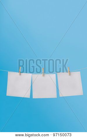 Three Blank Notes Pegged On Washing Line In Blue Sky