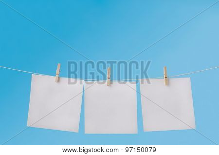 Three Blank Notes Pegged On Washing Line Against Blue Sky