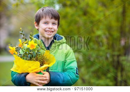 Cute smiling boy holding daffodils