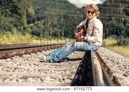 Happy Smiling Young Man With Guitar Sitting On Railway