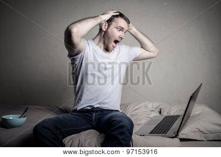 Desperate man looking at his laptop's monitor