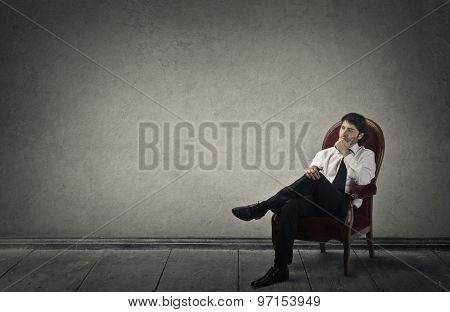 Young businessman sitting in a red chair