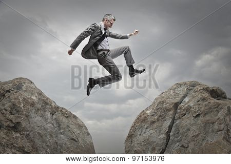 Manager jumping from a rock to another