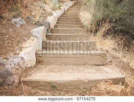 wooden steps going up a hill made out of stone and railroad tie blocks of wood