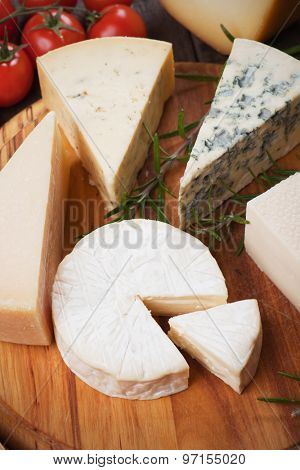 Assorted cheese on wooden platter, rich and healthy breakfast or snack food