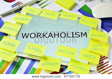 the text workaholism in a tablet computer full of sticky notes with different tasks,  placed on an office desk full of charts